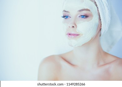 happy woman with a towel on her head puts on face mask