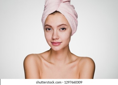 happy woman with a towel on her head on a gray background