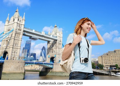 Happy woman travel in London with tower bridge, and smile to you, caucasian beauty