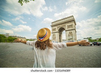Happy woman travel in Paris, Arc de Triomphe wearing France French hat, caucasian brunette traveling in Europe