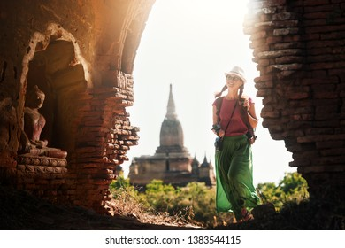 Happy woman traveler with backpack walking through the Bagan looking the ancient Buddhist stupas. Myanmar. Positive emotions. Concept of travel and adventure in Asia.