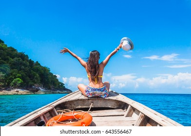 Happy woman traveler in bikini relaxing on boat her arms open feeling freedom, Andaman sea, Surin island, Phangnga,Travel in Thailand, Beautiful destination Asia, Summer holiday outdoors vacation trip