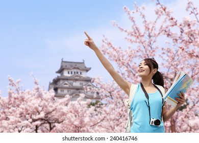 Happy woman traveler enjoy view with sakura cherry blossoms tree and castle on vacation while spring in japan, asian