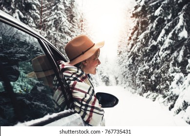 Happy woman traveler enjoying a snowy view of a forest winter road from the car window. Young hipster girl in vintage hat hanging out of the car window