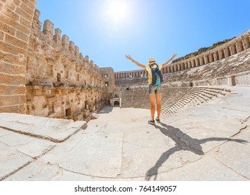 Happy woman traveler exploring the ruins of the ancient Greek amphitheater Aspendos in Turkey
