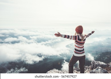 Happy woman traveler on mountain summit hands raised Travel Lifestyle success concept adventure active vacations outdoor over clouds harmony with nature