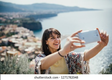 Happy woman traveler smiling at italian coast view.Woman traveling to European south coast.Enoying sunny weather mediterranean seaside.Taking selfie with smartphone front camera