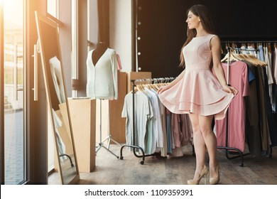 Happy woman trying on new dress in showroom. Fashion and choice concept