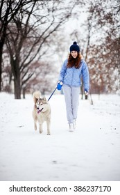 Happy woman of twenty-five years old walk in park in winter with dog Husky two years old