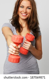 A happy woman with two dumbbells
