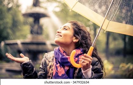 Happy woman under the rain smiling holding the umbrella