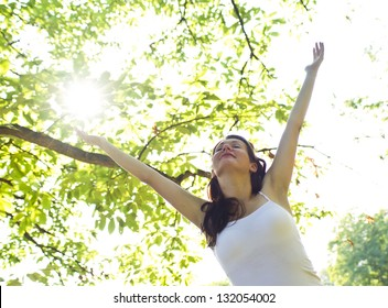 happy woman under a tree in summer