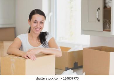 Happy woman unpacking in kitchen