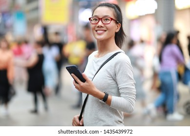 Happy woman use smartphone at city