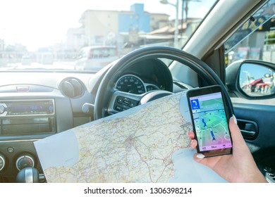 Happy woman uses a navigator in a smartphone while driving a car of Cyprus road. Traval vacation trip.
