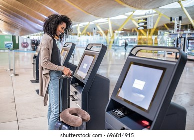 happy woman using the check-in machine at the airport getting the boarding pass.