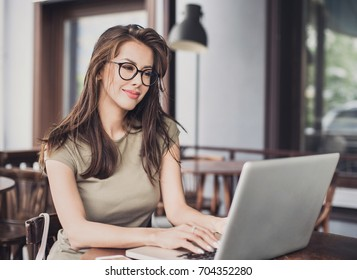 Happy woman using laptop at cafe. Young beautiful girl sitting in a coffee shop and working on computer