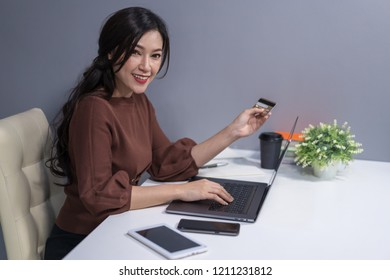 happy woman using laptop computer for online shopping with a credit card