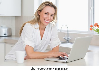 Happy woman using laptop at counter at home in the kitchen