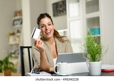 Happy woman using laptop and showing credit card for online shopping concept.