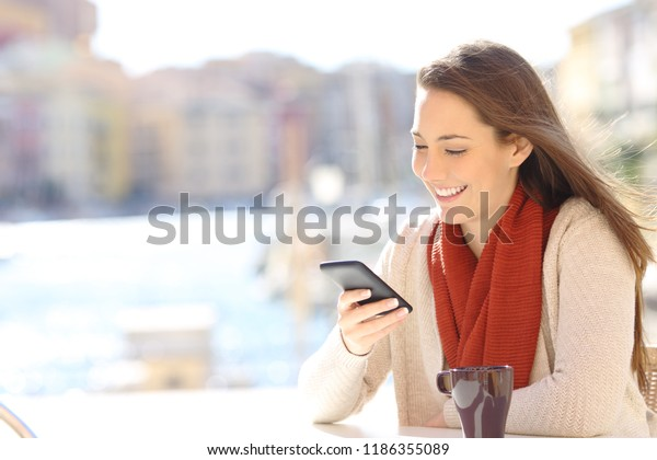Happy woman using a smart phone in a coffee shop on vacation in a coast town