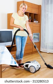 happy woman using vacuum cleaner during regular clean-up