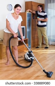 Happy woman vacuuming cleaning flat and her husband wiping furniture