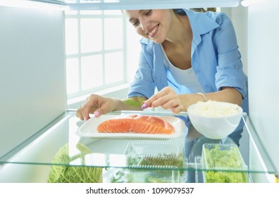 Happy Woman With Vegetables In Front Of Open Refrigerator, selective focus