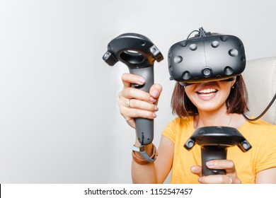 Happy woman with virtual reality headset and joystick playing VR games