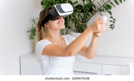 Happy woman in VR headset holding game controller and playing video games
