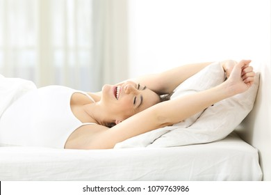 Happy woman waking up stretching arms lying on a bed at home