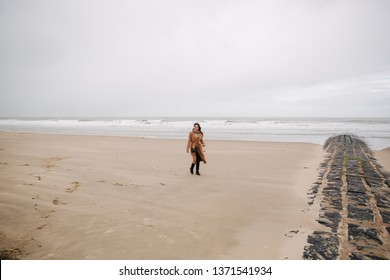Happy woman walkin on the beach along the North Sea. Outside is cold and rainy