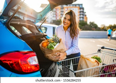 Happy woman walking to the car after shopping at the supermarket. Pretty Adult Woman Holding Groceries at Car. Busy woman after shopping in the supermarket
