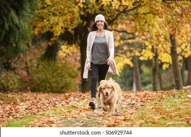 Happy woman walking her Golden Retriever Dog in a park with Fall