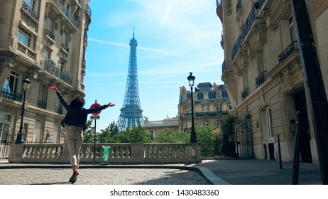 Happy woman walking and jumping the Camoens Avenue street rising hands wide open with eiffel tower on the background in Paris, traditional Paris buildings and neighbourhood