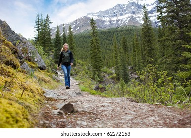A happy woman walking on a path on a mountain hike in Banff National Park