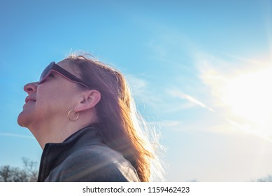 happy woman walking in park looking up on bright sunny day