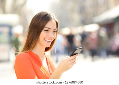 Happy woman walking in the street checking smart phone content