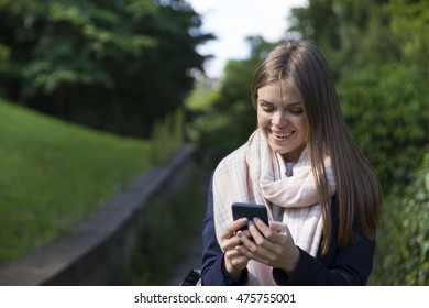 Happy woman walking and using her smart phone in the street. Caucasian female lifestyle concept.