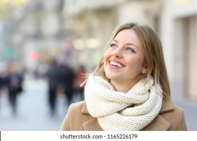 Happy woman warmly clothed looking above in winter in the street