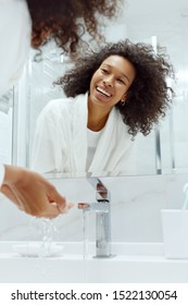 Happy woman washing hands in sink looking in mirror at bathroom. Portrait of beautiful happy african girl with afro hair going through morning beauty routine