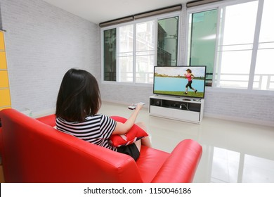 Happy woman watches television while sitting on the sofa.