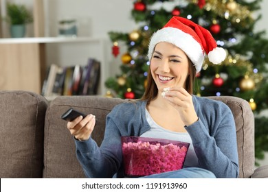 Happy woman watching christmas tv porgram sitting on a couch in the living room at home