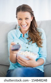 Happy woman watching television eating popcorn