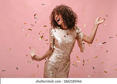 Happy Frau mit dunklem, dunklem Haar Stil in glänzenden trendigen Kleidung jubeln, Glas mit Champagner halten und mit Konfetti auf rosafarbenem Hintergrund posieren.