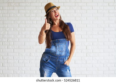 Happy woman wear denim overalls with straw hat and showing holding thumbs up, white wall on background