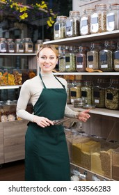 Happy woman wearing apron and selling nuts and dried fruits in organic shop