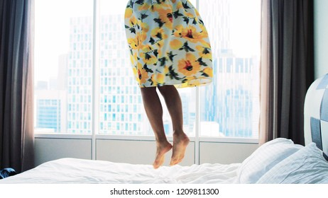 Happy woman wearing beautiful dress dances jumps on bed at home