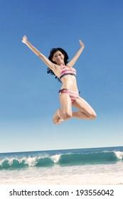 Happy woman wearing bikini jumping on the beach