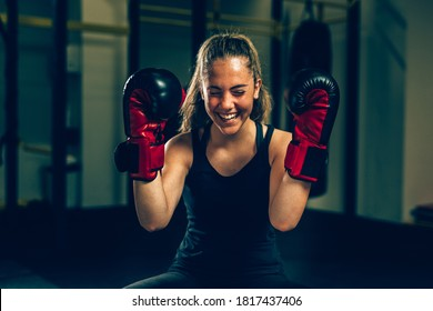 happy woman wearing boxing gloves in gym